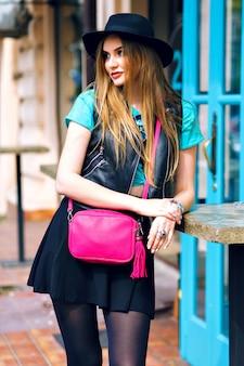 Moda plenerowa portret stylowej seksownej kobiety spacerującej samotnie, stylowy strój, mini spódniczka, czarna czapka i kurtka motocyklowa, jasne detale mody, pozytywny nastrój, lato, styl uliczny, centrum miasta.