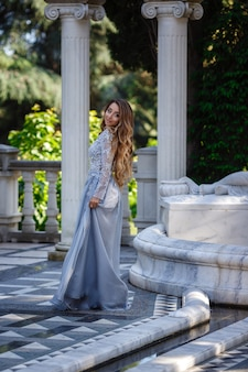 Moda plenerowa zdjęcie eleganckiej pięknej kobiety o blond włosach w luksusowej sukience z cekinami i srebrnymi dodatkami, pozuje w letnim parku