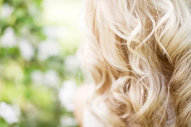 Moda plenerowa zdjęcie pięknej młodej kobiety w eleganckiej sukience pozuje w ogrodzie z kwitnącymi jabłoniami piękne strumieniowe blond loki widok z tyłu zdjęcie z bliska