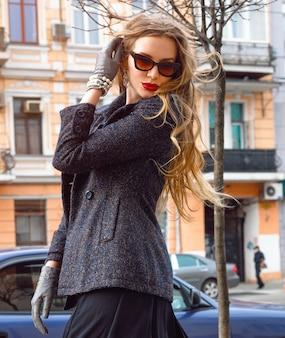 Moda portret całkiem stylowej młodej kobiety spacerującej samotnie na ulicy w starym europejskim mieście i bawić się, ubrana w eleganckie ubrania retro i okulary przeciwsłoneczne. styl vintage jesień.