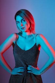 Moda portret dziewczyny światła neonowe lampy niebieski kolor czerwony.