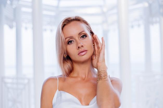 Moda portret europejskiej blondynki w jedwabnej białej letniej romantycznej sukni złotej bransoletki i kolczyków