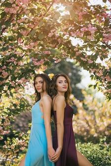 Moda portret fotografia dwóch kobiet w pobliżu kwitnących drzew na naturze
