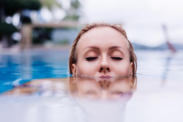Moda portret kaukaski kobieta w bikini w niebieskim basenie na wakacjach w naturalnym świetle coudy day