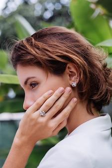 Moda portret kobiety w tropikalnej luksusowej willi na sobie białą stylową marynarkę i biżuterię na tropikalnych liściach