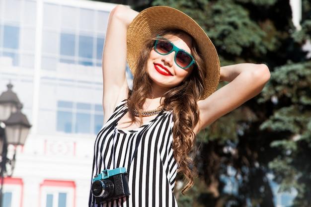 Moda portret kobiety z okulary i czerwone usta w kapeluszu