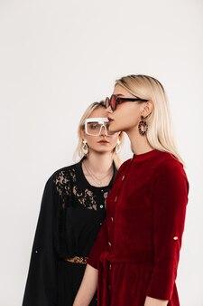 Moda portret młode atrakcyjne blondynki siostry kobiety w czerwono-czarnych modnych sukienkach w stylowych okularach w pobliżu szarej ściany vintage