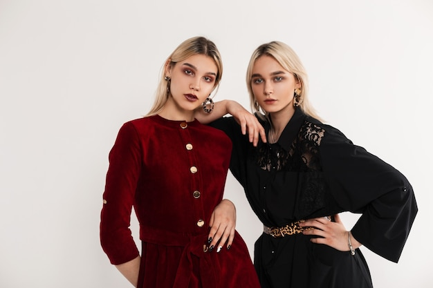 Moda portret młode atrakcyjne blondynki siostry kobiety w czerwonych i czarnych modnych sukienkach w pobliżu białej ściany vintage