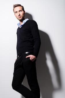 Moda portret młodego mężczyzny w czarnym swetrze i niebieskiej koszuli z kontrastowymi cieniami.