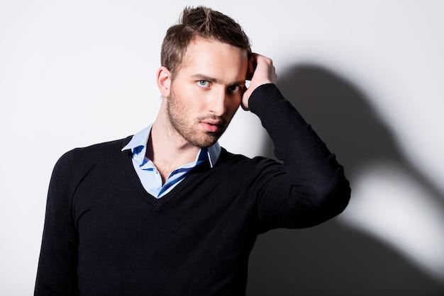 Moda portret młodego mężczyzny w czarnym swetrze pozuje na ścianie z kontrastowymi cieniami.