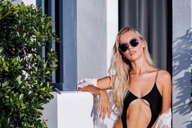 Moda portret młodej bogatej stylowej europejskiej kobiety w czarnym modnym stroju kąpielowym, okularach przeciwsłonecznych i koronkowej pelerynie na zewnątrz willi, tropikalne tło, ciepłe światło słońca.