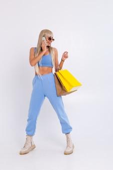 Moda portret młodej kobiety blondynka z długie wspaniałe proste włosy posiadają kolorowe torby na zakupy