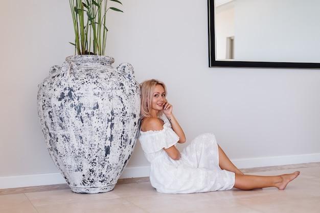 Moda portret młodej kobiety europejskiej o blond włosach w białej długiej letniej sukience
