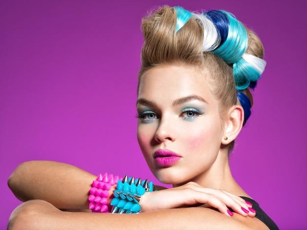 Moda portret młodej modelki rasy kaukaskiej z jasnym makijażem piękna kobieta z kreatywną fryzurą kobieta z makijażem fashion wspaniała twarz atrakcyjnej dziewczyny różowa ściana