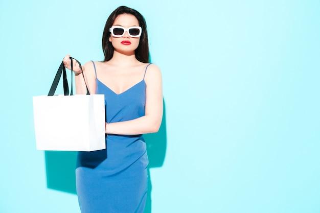 Moda portret młodej pięknej kobiety brunetka ubrana w ładną niebieską letnią sukienkę