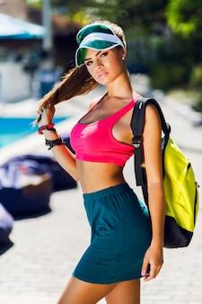 Moda portret młodej pięknej kobiety w stylowym mundurze sportowym z neonowym plecakiem i przezroczystym daszkiem pozuje na zewnątrz w słoneczny letni dzień.
