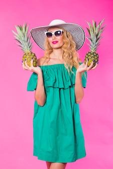 Moda portret młodej pięknej kobiety z ananasem na różowym tle
