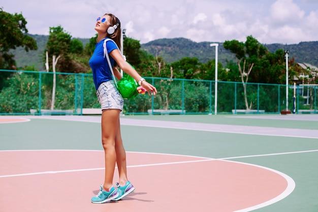 Moda portret młodej, sprawnej, sportowej kobiety pozującej latem na świeżym powietrzu dostał słoneczny dzień, nosząc jasne neonowe ubrania sportowe z powrotem i okulary przeciwsłoneczne.