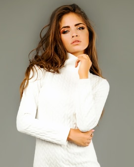 Moda portret młodej szczęśliwej ładnej kobiety w białej sukni na szarej ścianie