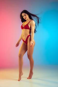 Moda portret młodej wysportowanej i wysportowanej kobiety w stylowych czerwonych luksusowych strojach kąpielowych na gradientowej ścianie idealne ciało gotowe na lato
