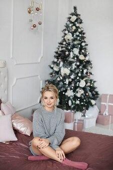 Moda portret modelki z doskonałym makijażem i fryzurą w pomieszczeniu z choinką w tle. śliczna blondynka w przytulnej sukience z dzianiny na łóżku w noworocznym wystroju wnętrza