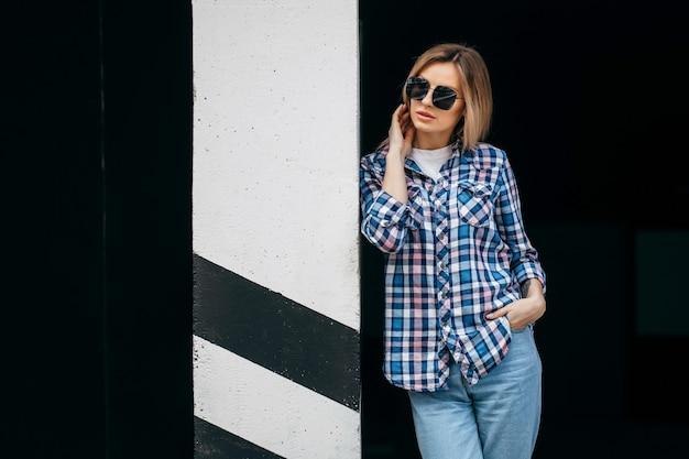 Moda portret pięknej kobiety z piękną twarz na sobie koszulę w kratę grunge pozowanie samotnie