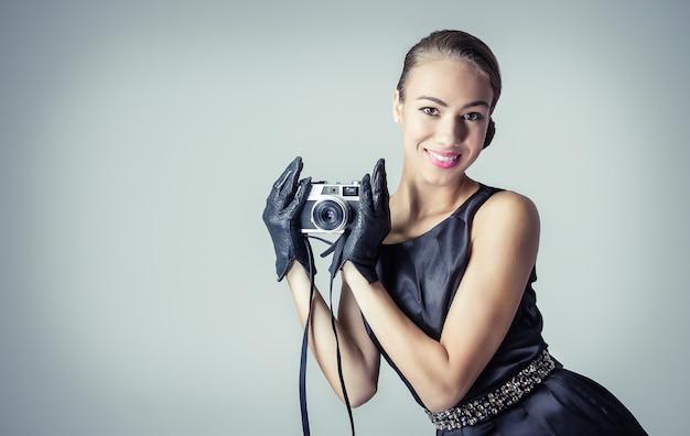 Moda portret pięknej młodej dziewczyny w klasycznym stylu vintage z analogowym aparatem fotograficznym