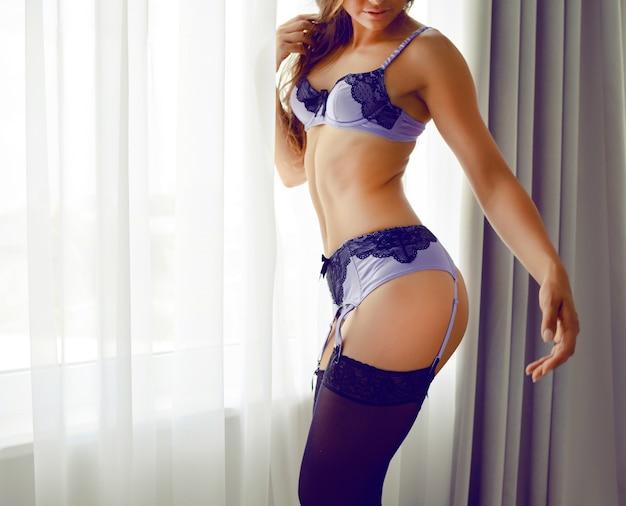 Moda portret portret młodej seksownej kobiety o doskonałej szczupłej sylwetce sportowej, ubrana w stylową piękną bieliznę, pozowanie samotnie w pobliżu okna styl buduarowy, romantyczna atmosfera.
