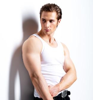 Moda portret przystojny młody mężczyzna w białej koszuli patrząc z ukosa pozuje na ścianie z kontrastowymi cieniami.
