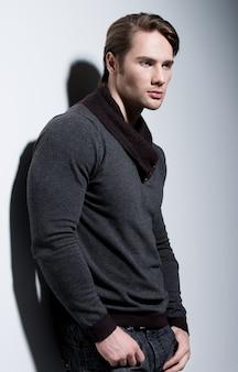 Moda portret seksownego przystojnego mężczyzny w szarym swetrze pozuje na ścianie z kontrastowymi cieniami i patrzy w bok.