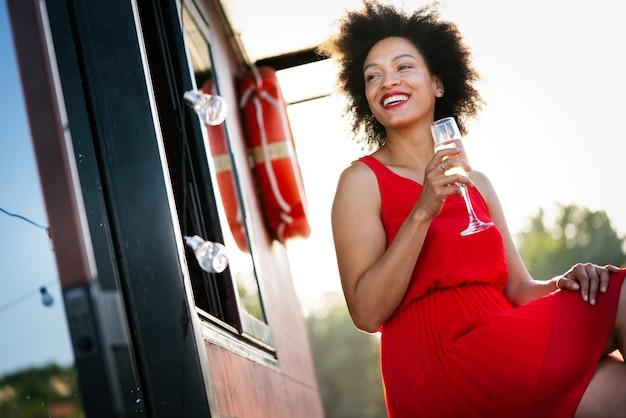 Moda portret seksownej ładnej afrykańskiej kobiety z napojem na świeżym powietrzu