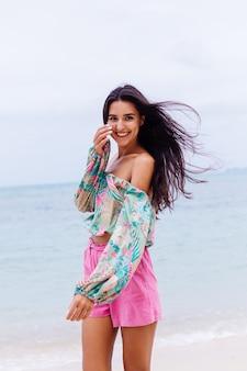 Moda portret stylowej kobiety w kolorowy print top z długim rękawem i różowe szorty na plaży, tropikalne tło.