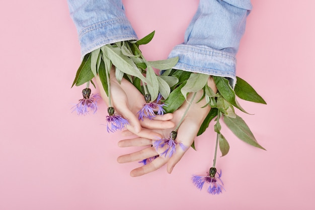 Moda ręcznie robione kwiaty rosną z rękawów naturalnych kosmetyków kobiet, pięknych kwiatów ręcznie z jasnym kontrastowym makijażem, pielęgnacji dłoni