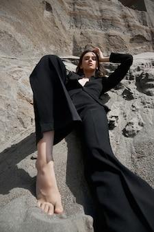 Moda sexy kobieta w garniturze pozowanie na skałach piasku. nowoczesna niezależna dziewczyna, piękny makijaż