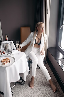 Moda sexy młoda kobieta w modnym stroju pozowanie siedząc przy stole z luksusowym jedzeniem i piciem, patrząc na okno. glamour uwodzicielska kobieta w bieliźnie i stylowo ubiera się relaksująco ciesząc się bogatym stylem życia