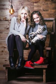 Moda śliczna mała dziewczynka i piękna kobieta z brytyjskim kotkiem w ramionach bardzo szczęśliwi razem