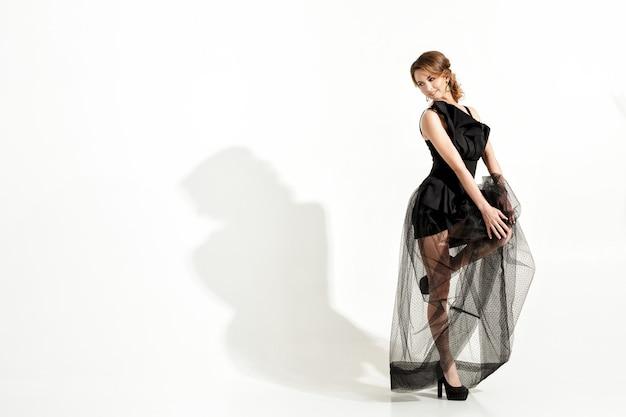 Moda strzał elegancka i seksowna młoda kobieta w czarnej sukience i welonie na białym tle
