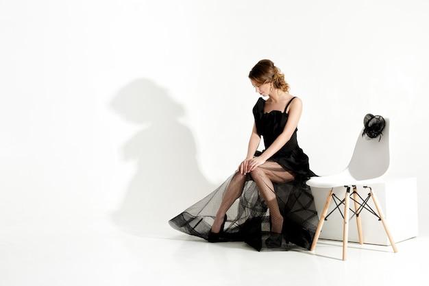 Moda strzał eleganckiej smutnej kobiety w czarnej sukience i welonie siedzi na krześle i czeka na białym tle