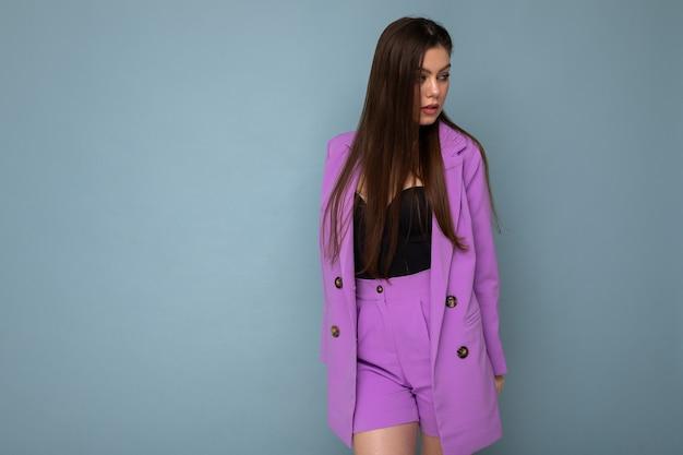 Moda strzał młoda seksowna szczęśliwa atrakcyjna brunetka kobieta ubrana w stylowy fioletowy garnitur na białym tle