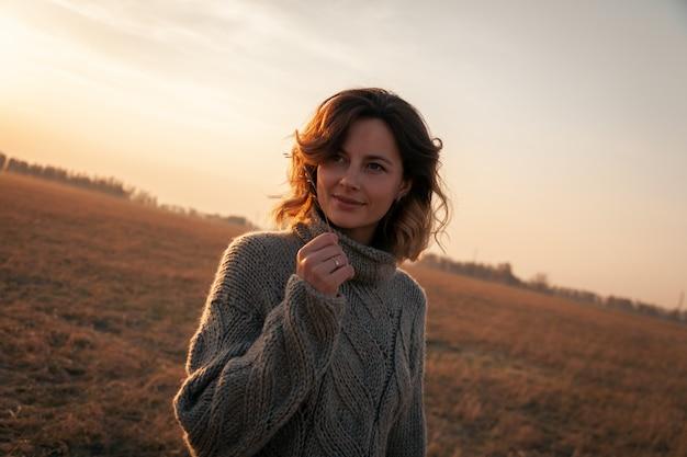 Moda styl życia portret młodej kobiety modne ubrane w brązowy sweter z dzianiny.