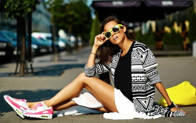 Moda stylowa piękna młoda brunetka kobieta model w lecie hipster kolorowe ubranie pozowanie na tle ulicy
