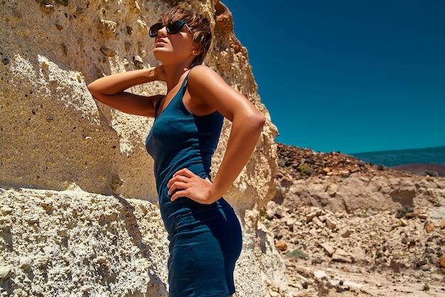Moda stylowa piękna młoda brunetka kobieta model w letnią niebieską sukienkę pozowanie w pobliżu piasku skały