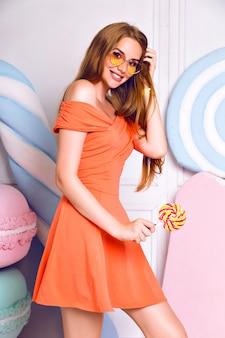 Moda stylowy ładny portret niesamowitej blondynki, pozująca w pobliżu słodyczy gigantycznej twarzy, sklep ze słodyczami, modna sukienka śmieszne okulary przeciwsłoneczne, pozytywny nastrój.