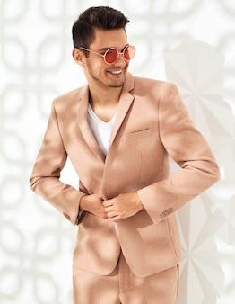 Moda stylowy model ubrany w elegancki jasnoróżowy garnitur pozowanie w pobliżu białej ścianie