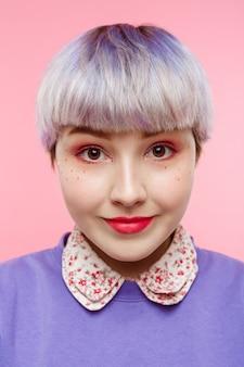 Moda szczegół portret smling pięknej laleczkowej dziewczyny z krótkimi jasnofioletowymi włosami na sobie liliowy sweter na różowej ścianie