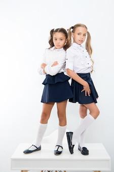 Moda szkolna. moda dziecięca dla małych dziewczynek w mundurkach szkolnych. małe dziewczynki na białym tle.