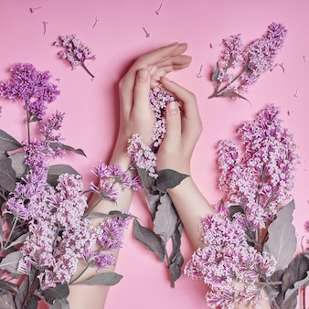 Moda sztuka ręce naturalne kosmetyki kobiety, jasne fioletowe kwiaty bzu w parze z jasnym kontrastowym makijażem, pielęgnacja dłoni. kreatywnie piękno fotografia kobiety obsiadanie przy stołem