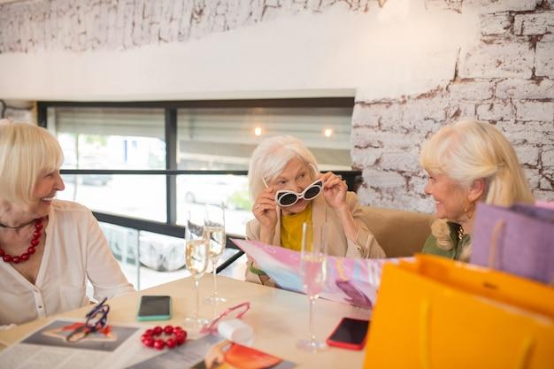 Moda. trzy kobiety dobrze się bawią podczas przymierzania nowych okularów przeciwsłonecznych