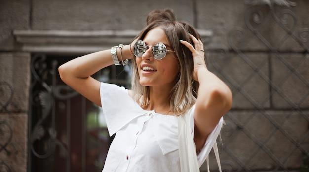 Moda uliczna. portret stylowe blond kobieta w modne ubrania i okulary przeciwsłoneczne, pozowanie na zewnątrz przed starą architekturą