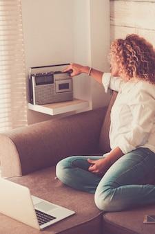 Moda urocza kręcone młoda kobieta w domu przy użyciu starej i nowej technologii siedzącej na kanapie - koncepcja vintage i używane radio z lat 80. - ludzie w domu w pomieszczeniach rekreacyjnych słuchając muzyki